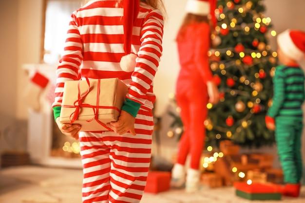 Mała dziewczynka chowa prezent za plecami w wigilię
