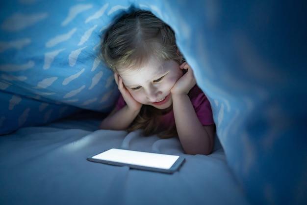 Mała dziewczynka chowa się pod kocem ze smartfonem w nocy, kiedy wszyscy śpią.