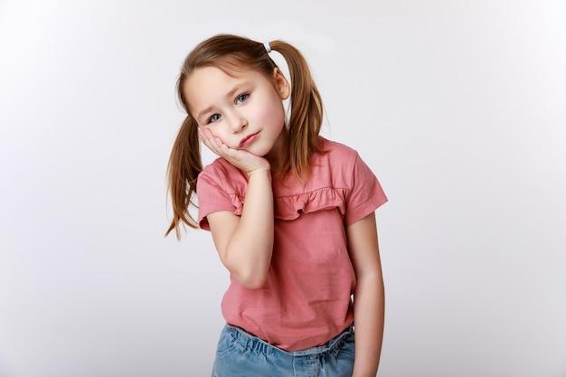 Mała dziewczynka cierpiąca na ból zęba, trzymając się za policzek