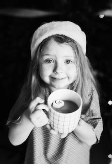 Mała dziewczynka cieszy się kubek gorąca czekolada