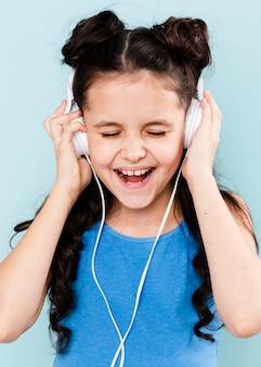 Mała dziewczynka cieszy się muzykę przy hełmofonami