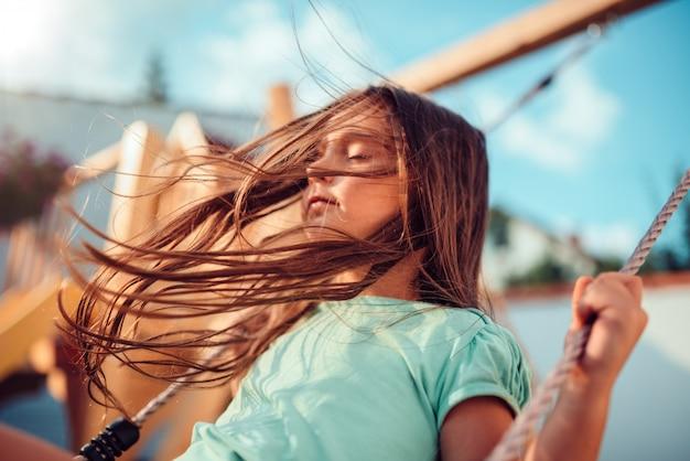 Mała dziewczynka cieszy się na huśtawce z zamkniętymi oczami i długie włosy lataniem