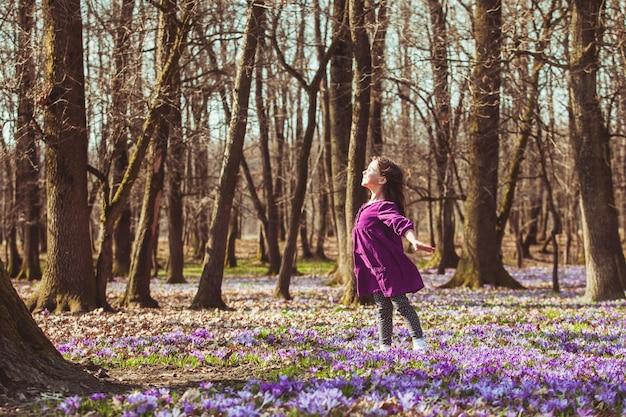 Mała dziewczynka cieszy się słońcem, marzy i lata, inspirowana kwitnącą łąką szafranów