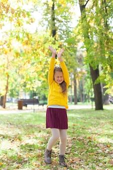 Mała dziewczynka cieszy się w parku miejskim.