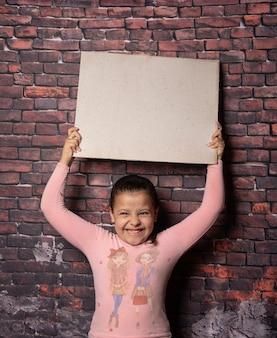 Mała dziewczynka co pozuje z pustymi literami z recyklingu przed starym tłem ściany cegła, ciemne tło, selektywne focus.