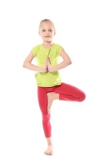 Mała dziewczynka ćwiczy jogę na białym