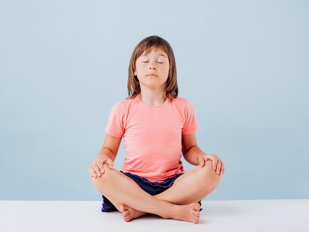 Mała dziewczynka ćwiczy jogę na niebieskim tle