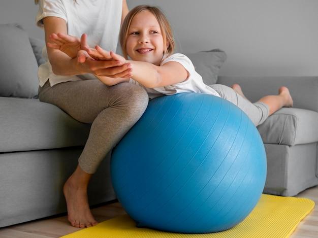 Mała dziewczynka ćwiczy na piłce