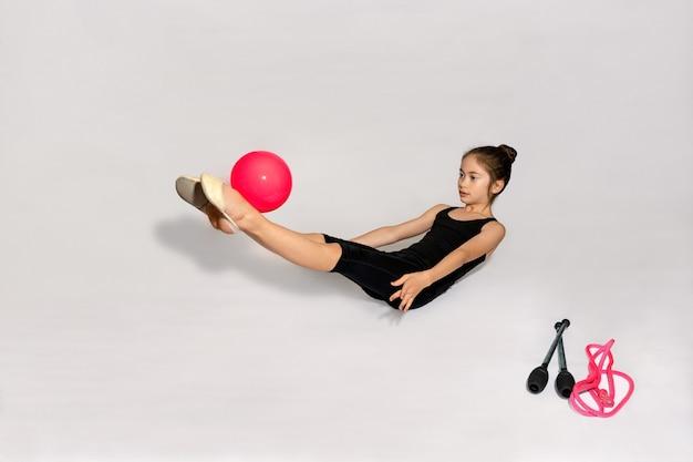 Mała dziewczynka ćwiczy z piłką na podłodze