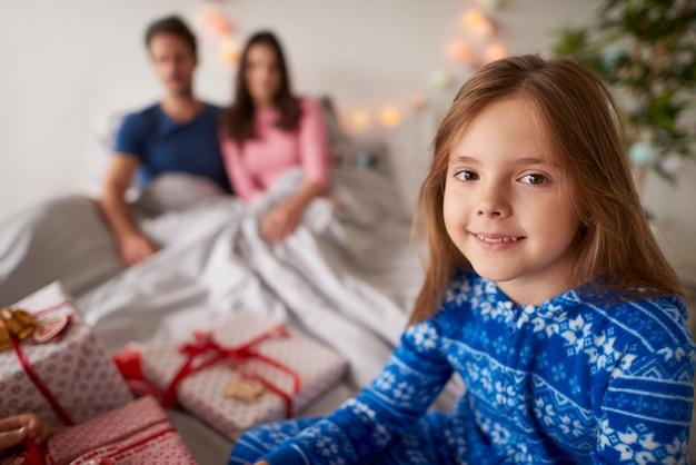 Mała dziewczynka czeka na otwarcie prezentów świątecznych