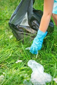Mała dziewczynka czyści plastikowe śmieci na zielonej trawie w parku