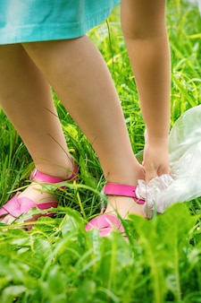 Mała dziewczynka czyści plastikowe torby na zielonej trawie w parku
