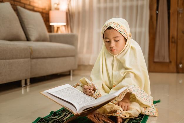 Mała dziewczynka czyta koran będący ubranym muzułmańskiego hidżab
