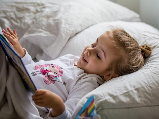 Mała dziewczynka czyta książkę dla dzieci w łóżku po śnie