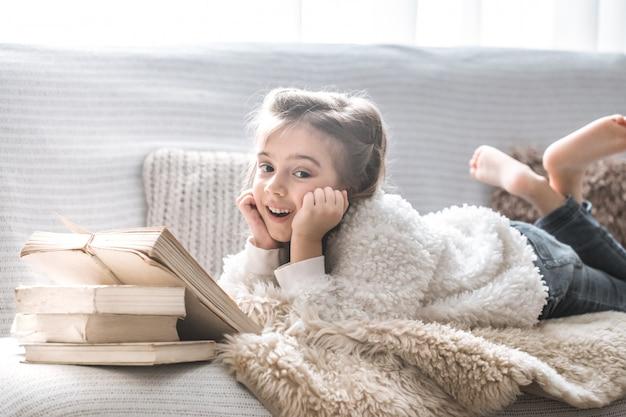 Mała dziewczynka czyta książkę na wygodnej kanapie, piękne emocje