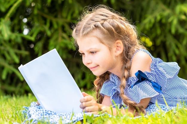 Mała dziewczynka czyta książkę na zielonej trawie.