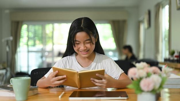 Mała dziewczynka czyta książkę przy drewnianym biurku. koncepcja studia w domu.