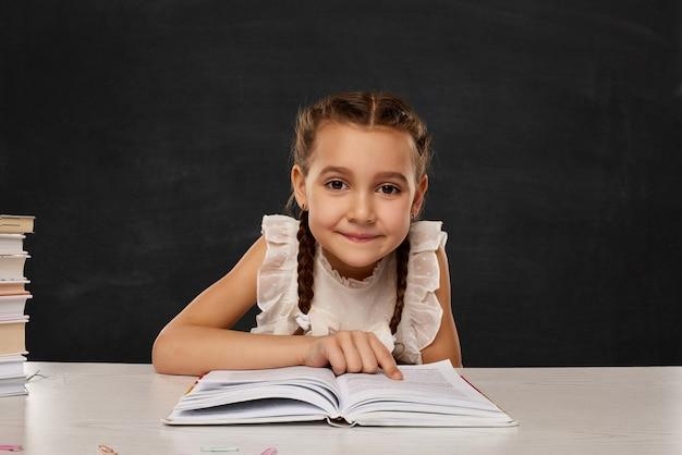 Mała dziewczynka czyta książkę w klasie