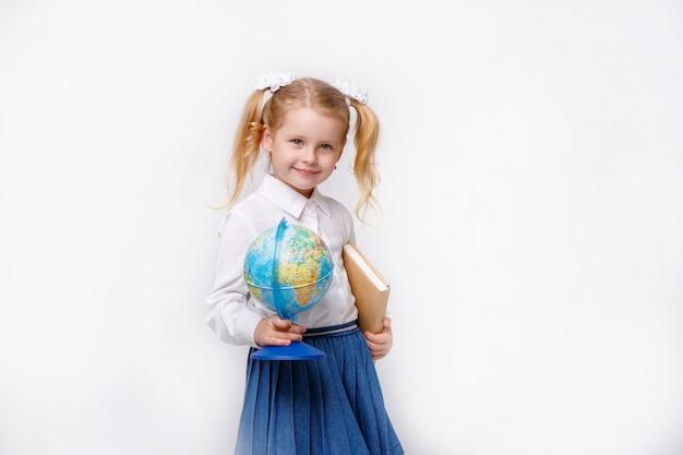 Mała dziewczynka czyta książkę w mundurku szkolnym na białym tle