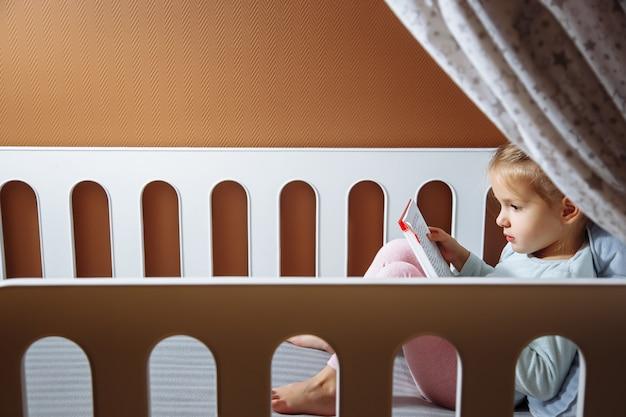Mała dziewczynka czyta książkę w sypialni