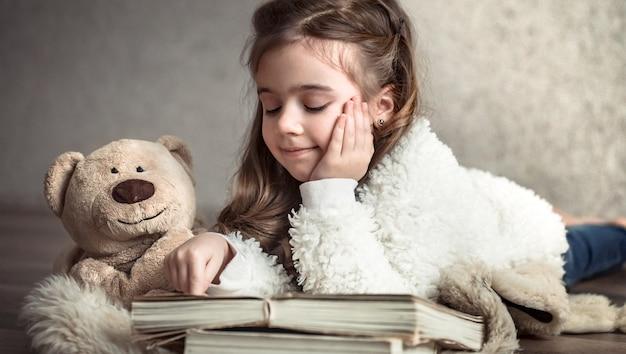 Mała dziewczynka czyta książkę z misiem na podłodze, pojęcie relaksu i przyjaźni