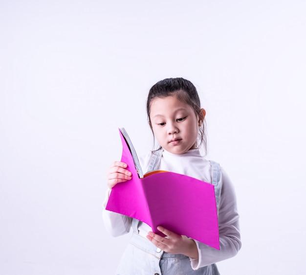 Mała dziewczynka czyta książkę z zainteresowaniem, inteligentne dzieci