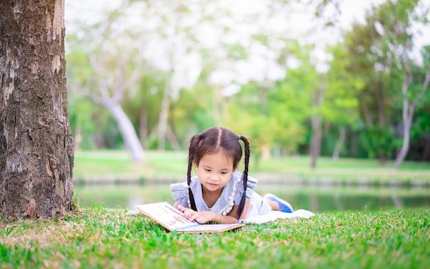 Mała dziewczynka czytając książkę leżąc w parku
