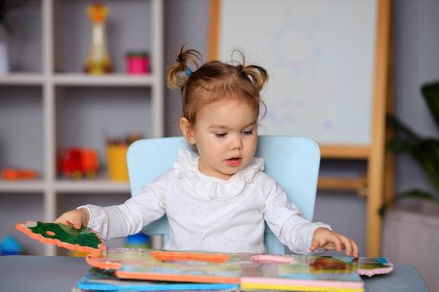 Mała dziewczynka czytając książkę przy stole