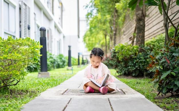 Mała dziewczynka czytając książkę z plecakiem siedzi w parku gotowy do szkoły