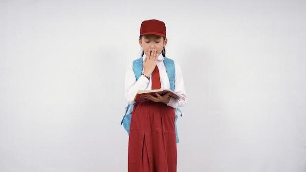 Mała dziewczynka czytanie w szkole podstawowej, aby zaskoczyć na białym tle
