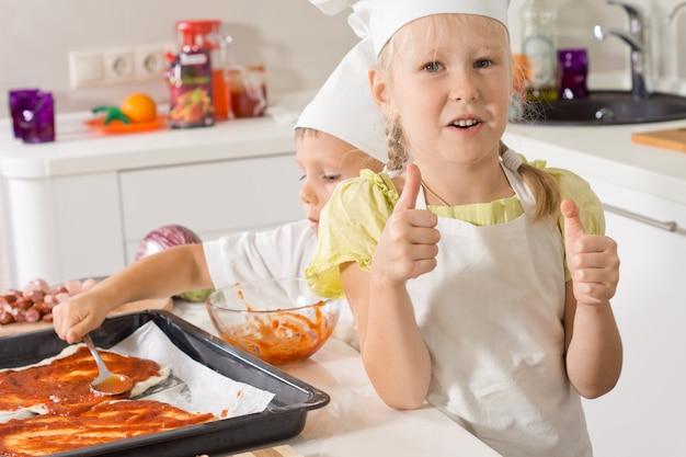 Mała dziewczynka daje kciuki do góry, kiedy piecze pizzę