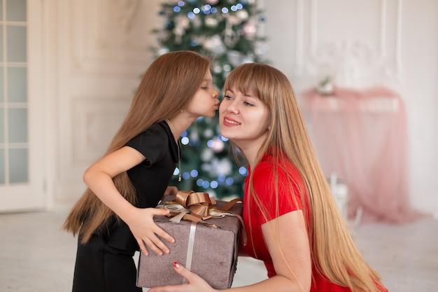 Mała dziewczynka daje mamie pudełko z prezentem świątecznym.