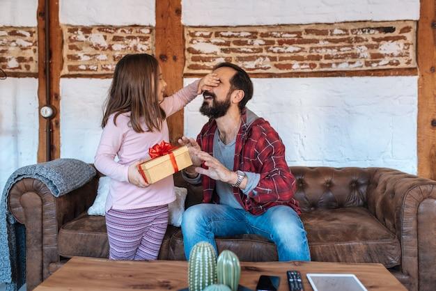 Mała dziewczynka daje niespodzianka prezentowi o jej ojciec na kanapie w domu na ojca dniu