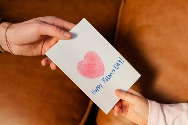 Mała dziewczynka daje ojcu kartkę na dzień ojca