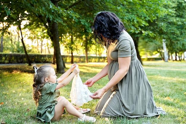 Mała dziewczynka daje swoją małą sukienkę ciężarnej mamie dla sis.