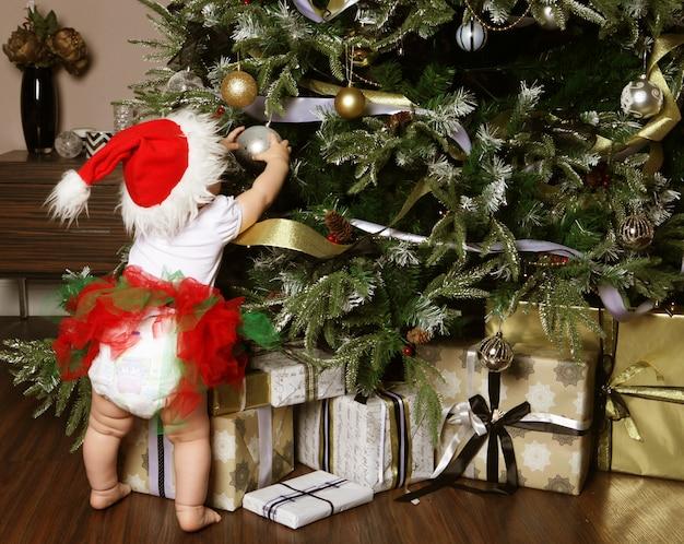 Mała dziewczynka dekorowanie choinki zabawki, wakacje, prezent, grudzień