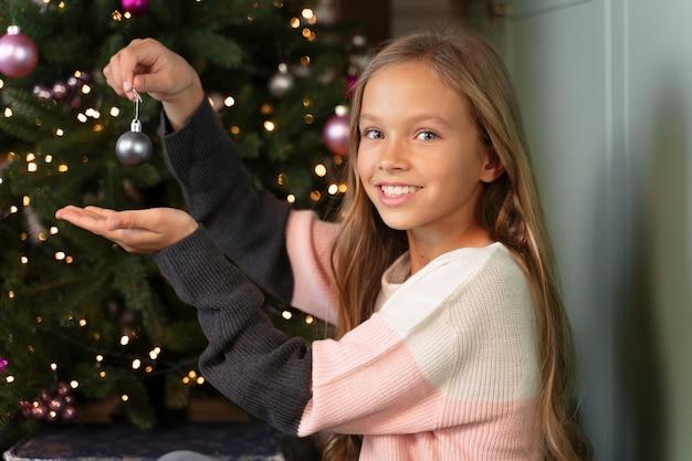 Mała dziewczynka dekoruje choinkę