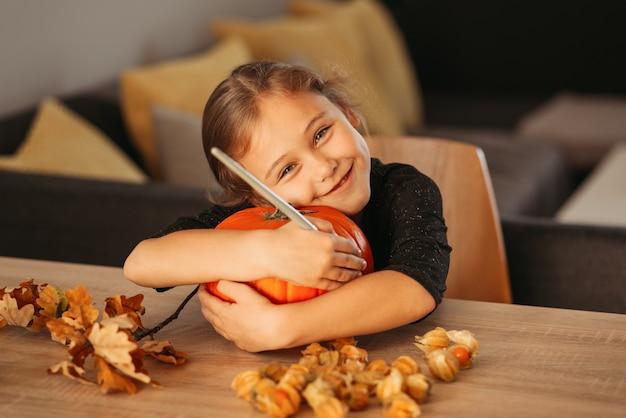 Mała dziewczynka dekoruje dynię w pokoju na halloween. dzieci dekorują dom. dzieci rzeźbią dynię. upiorna zabawa na halloween