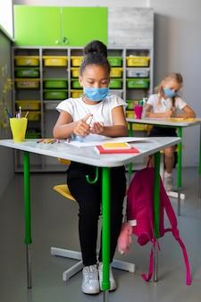 Mała dziewczynka dezynfekuje w klasie