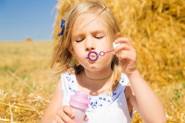 Mała dziewczynka dmucha bąble przeciw stogowi siana