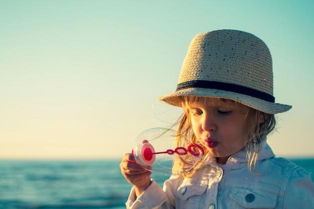 Mała dziewczynka dmucha mydlanych bąble przy morzem. stonowane zdjęcie