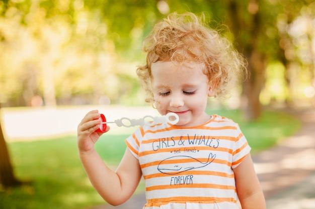 Mała dziewczynka dmucha mydlanych bąble