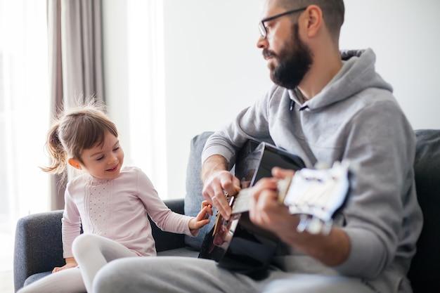 Mała dziewczynka dotyka strun gitary