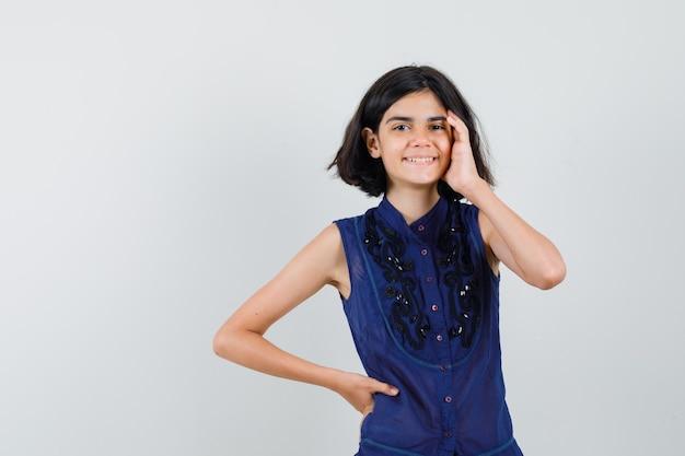 Mała dziewczynka dotyka twarzy ręką w niebieskiej bluzce i szuka zawstydzonego