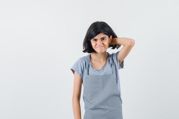 Mała dziewczynka drapanie głową w t-shirt, fartuch i wyglądający na zawstydzonego, widok z przodu.