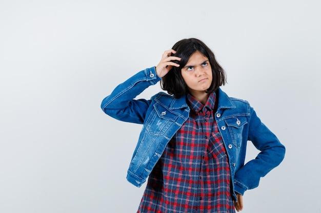 Mała dziewczynka drapie się po głowie w koszulę, kurtkę i patrząc zamyślony. przedni widok.