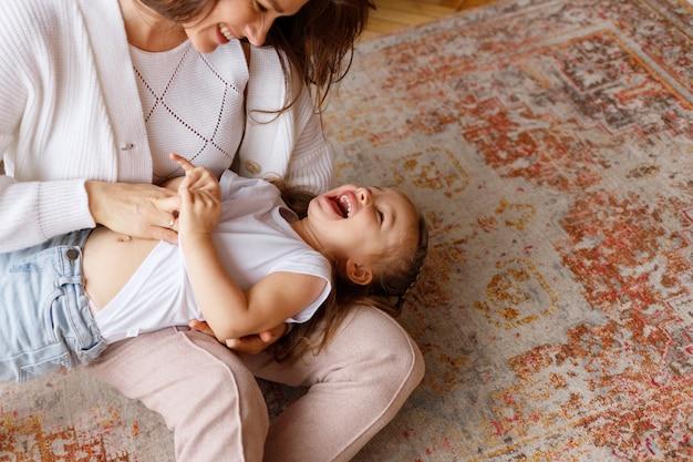 Mała dziewczynka dużo się śmieje w ramionach mamy