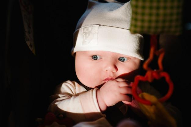 Mała dziewczynka dziecko bawi się zabawkami niemowlę leży w foteliku samochodowym i uśmiecha się