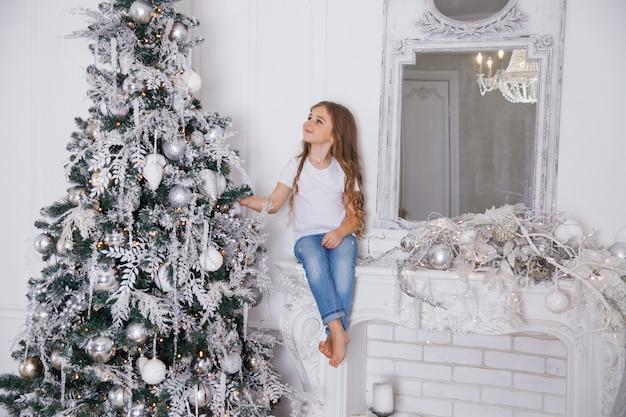 Mała dziewczynka dziecko dekorowanie choinki w białym klasycznym wnętrzu siedzi na kominku z lustrem. wesołych świąt, szczęśliwego nowego roku, wesołych świąt.