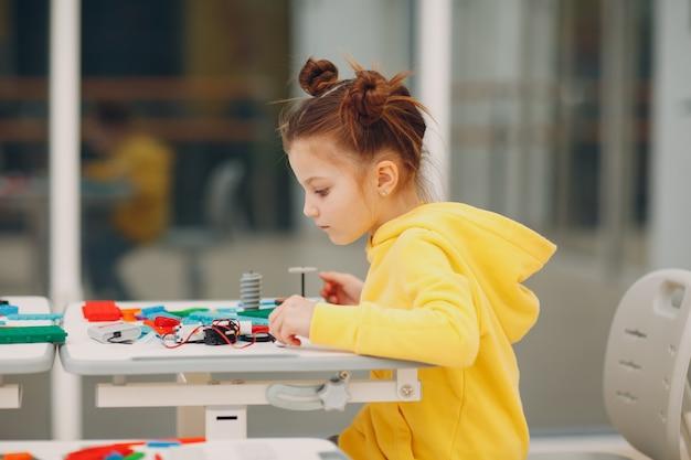 Mała dziewczynka dziecko dziecko konstruktor sprawdzania zabawki techniczne. konstruktor robotyki dzieci montuje robota.